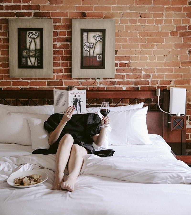 Une fille en train de lire un livre et boire un verre de vin dans un lit de l'Hôtel Nelligan