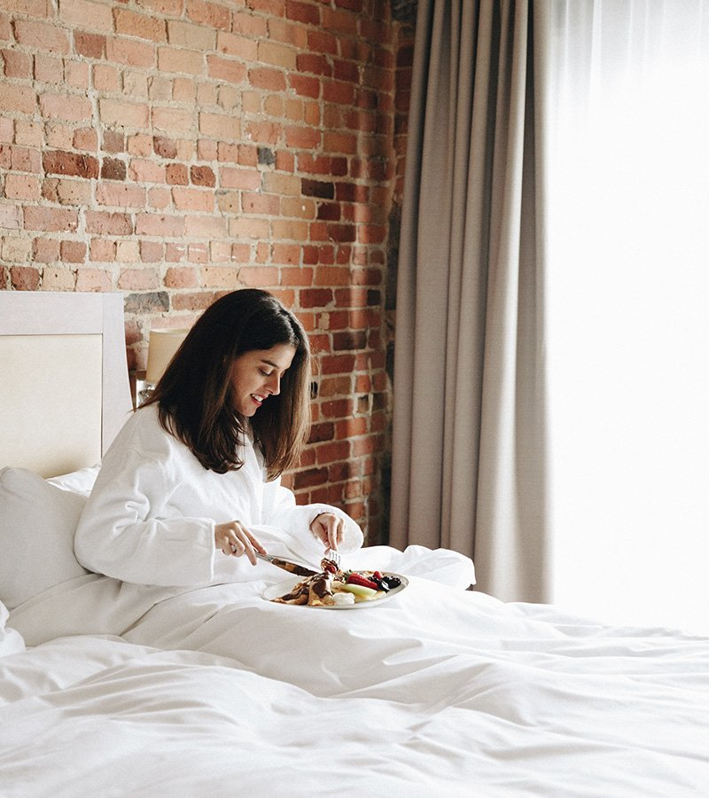 A girl eating a breakfast in bed in one of the rooms of Hôtel Nelligan.