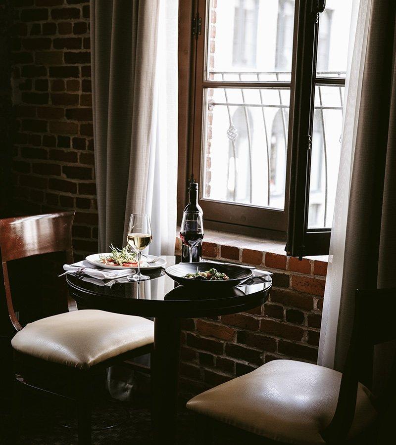 Un repas servi sur une table devant une fenêtre dans une des chambres de l'Hôtel Nelligan