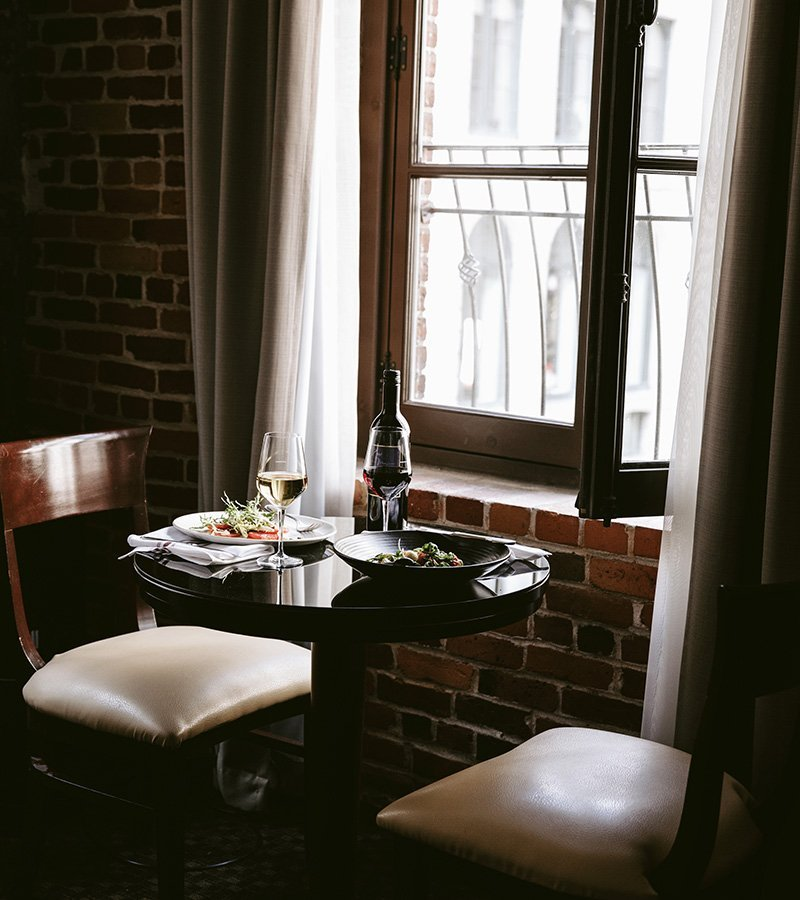 A dinner served in a table in front of a window in one of the rooms of Hôtel Nelligan