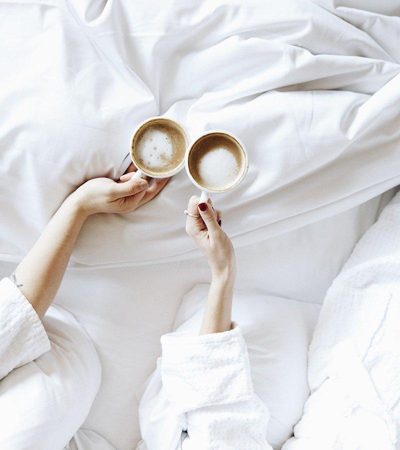 Deux personnes en train de boire des chocolats chauds dans le lit dans l'une des chambres de l'Hôtel Nelligan