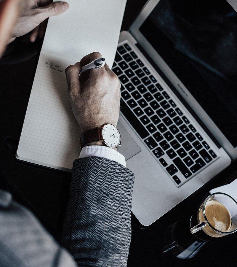 Un homme portant une montre en train d'écrire sur un papier et avec un ordinateur portable ouvert devant lui.
